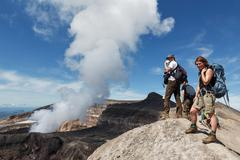 Tourists in crater of active volcano watching at volcano fumaroles. Kamchatka Stock Photos