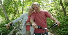 Happy mature couple smiling with bikes looking at camera Stock Footage