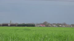 Train passes on the tracks on the horizon among agricultural fields, 4k Stock Footage