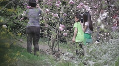 Asian girl photographed on a background of flowering trees in a Park in spring Stock Footage