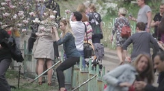 A lot of people walk the flowery Park Stock Footage