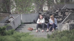 Two young girls sitting on the steps barefoot and relax Stock Footage