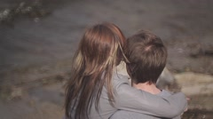 a girl and a guy sitting on the bank of the river and kissing - stock footage