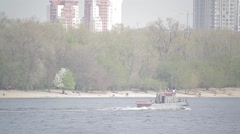 A small boat floats on the river in the beach in a big city Stock Footage