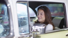 4K Smiling woman sitting in classic car takes the keys from garage worker - stock footage