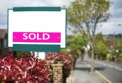 SOLD sign outside a house on a street - stock photo
