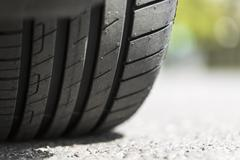 Close up of car tyre tread on the road - stock photo