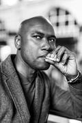 Handsome man in the city smoking a cigarette - stock photo