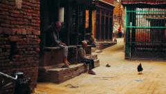 Locals rest among shrines and historic buildings in Bhaktapur, Nepal Stock Footage