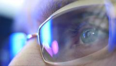 Reflection in the eye and glasses of the monitor when watching an action movie - stock footage
