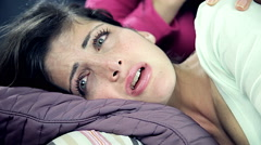 Two sad female friends holding each other in bed closeup Stock Footage