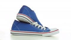 Blue sneakers revolve on a white background Stock Footage