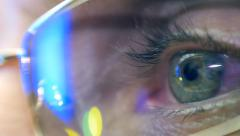 Reflection in the eye and glasses of the monitor when watching an action movie Stock Footage