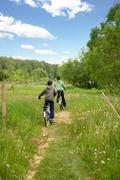 Two children on bicycles in the country Stock Photos