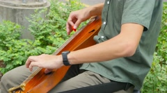 Singapore, young street misician plays folk instrument on Orchad Road. Stock Footage
