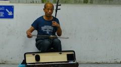 Hong Kong, old man playing chineese folk music on the street. Stock Footage