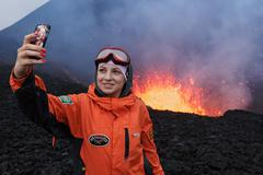 Eruption volcano, girl photographed selfie on background lava lake in crater Kuvituskuvat