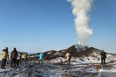 People watching the eruption volcano, ejecting lava, ash, steam and gas Stock Photos