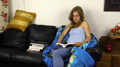 Pregnant woman read book on sofa and caress her stomach belly Stock Footage