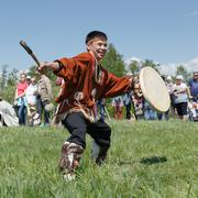 Man in clothes indigenous people of Kamchatka dancing with a tambourine - stock photo