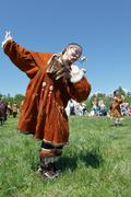 Girl in clothing aborigine of Kamchatka dancing on the green grass. Kamchatka - stock photo