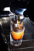 Espresso machine brewing a coffee. Coffee pouring into shot glasses - stock photo