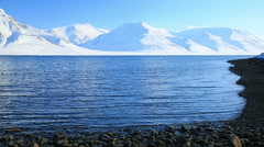 The waves of the Arctic Ocean and the snow-capped mountains. - stock footage