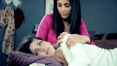 Two sad female friends holding each other in bed medium shot Stock Footage
