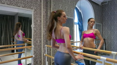 Flexible girl  pole dancer warms up body in training hall.  4K 3840x2160 Stock Footage