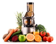 Slow juicer with organic fruits and vegetables isolated on white. Detox diet Stock Photos