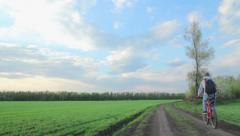 Dirt road,man rides a bicycle,landscape,green field,a field in spring Stock Footage
