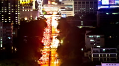 Bangkok aerial night time-lapse streaming traffic with distant sky-train bridges Stock Footage