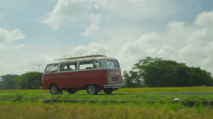 A two-tone red and white retro van (bus) driving through rice fields. Stock Footage