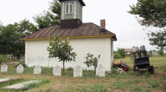 Century old chapel building, cemetery, steeple, tombstones, countryside Stock Footage