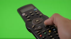Changing channels  with remote control in hand on green screen  Stock Footage