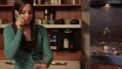 Young Woman on the phone in a modern kitchen Stock Footage