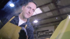 4K Mechanic in auto repair shop wiping down the bodywork of classic car - stock footage