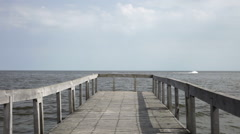 Old wooden pier pontoon, sea water view of clear sky and jet ski  - stock footage