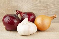 Onions,red onions and garlic on wooden background plank - stock photo
