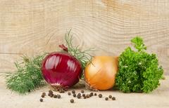 Onion,red onion,dill,parsley,allspice and black pepper on wooden background Stock Photos