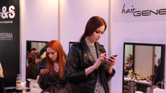 Super model checks her smartphone during a break for text messages Stock Footage