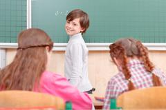 Little boy standing near blackboard - stock photo