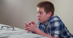 Frustrated young boy kneeling against bed 4k - stock footage