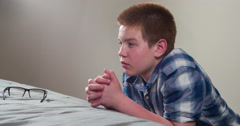 Boy thinking and praying next on bed 4k - stock footage