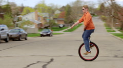 Young man in sunglasses rides unicycle in suburbia 4K Stock Footage