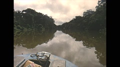 Vintage 16mm film, Amazon native tribe boating up river 1960s Stock Footage