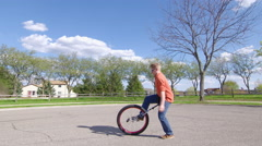 Young man trying to get on a unicycle 4K Stock Footage