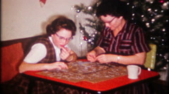 2007 - mother & daughter put together a picture puzzle - vintage film home movie Stock Footage