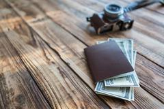 Blank passport and camera with US dollars on wood table Stock Photos