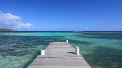 Wooden dock extending into tropical turquoise sea Stock Footage